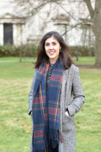 Sophia is looking into the camera and grinning. She is wearing a grey coat and is standing against a grassy space with some trees and a building in the distance.