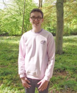 Liam is grinning and looking at the camera. He is wearing a pink CUSU LGBT+ jumper, and the background is a woody area