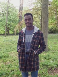 Tochi is smiling and looking at the camera. He is wearing a black and red checked hoodie. The background is a wooded area.