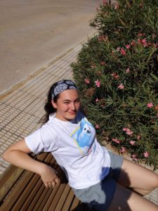 Grace is looking into the camera and smiling. Grace is sitting on a bench in bright sunlight, and there is an oleander bush in the background