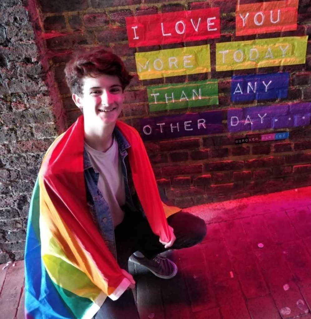 """Louis is smiling and wearing a rainbow flag. He is crouching in front of a rainbow wall with the words """"I love you more today than any other day..."""" printed on it."""