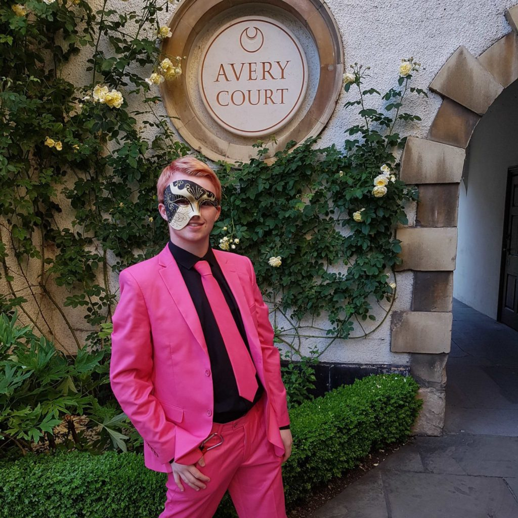 Alfie, a white Demiboy, getting hyped for Rainbow Ball 2018. They are wearing a hot pink suit jacket, trousers and tie with a black shirt, a masquerade ball mask, and faded pink hair. They are posing in front of the sign for Avery Court, Trinity Hall, with an archway and shrubbery in the background.