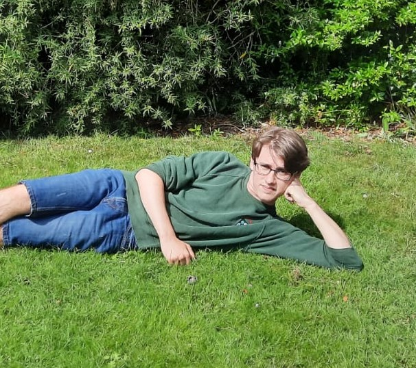 Zac is reclining on a patch of grass wearing a green college sweater and a pair of shorts. He looks slightly bemused, possibly because sunlight is shining in his face.