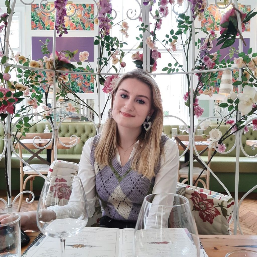 Olivia, a white woman, is sitting in front of a floral background. She is wearing a purple, green and white sweater vest, layered over a white shirt, with matching earrings! She has blonde hair and is smiling at the camera.