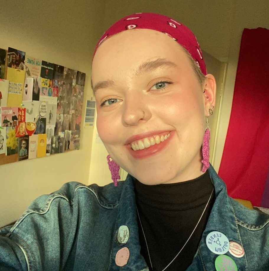 Hanna is smiling broadly at the camera, wearing a purple bandana on their head. She is wearing a black turtleneck and a denim jacket with colourful pins. The photo is taken in sunset lighting, with a pinboard and bisexual pride flag in the background.