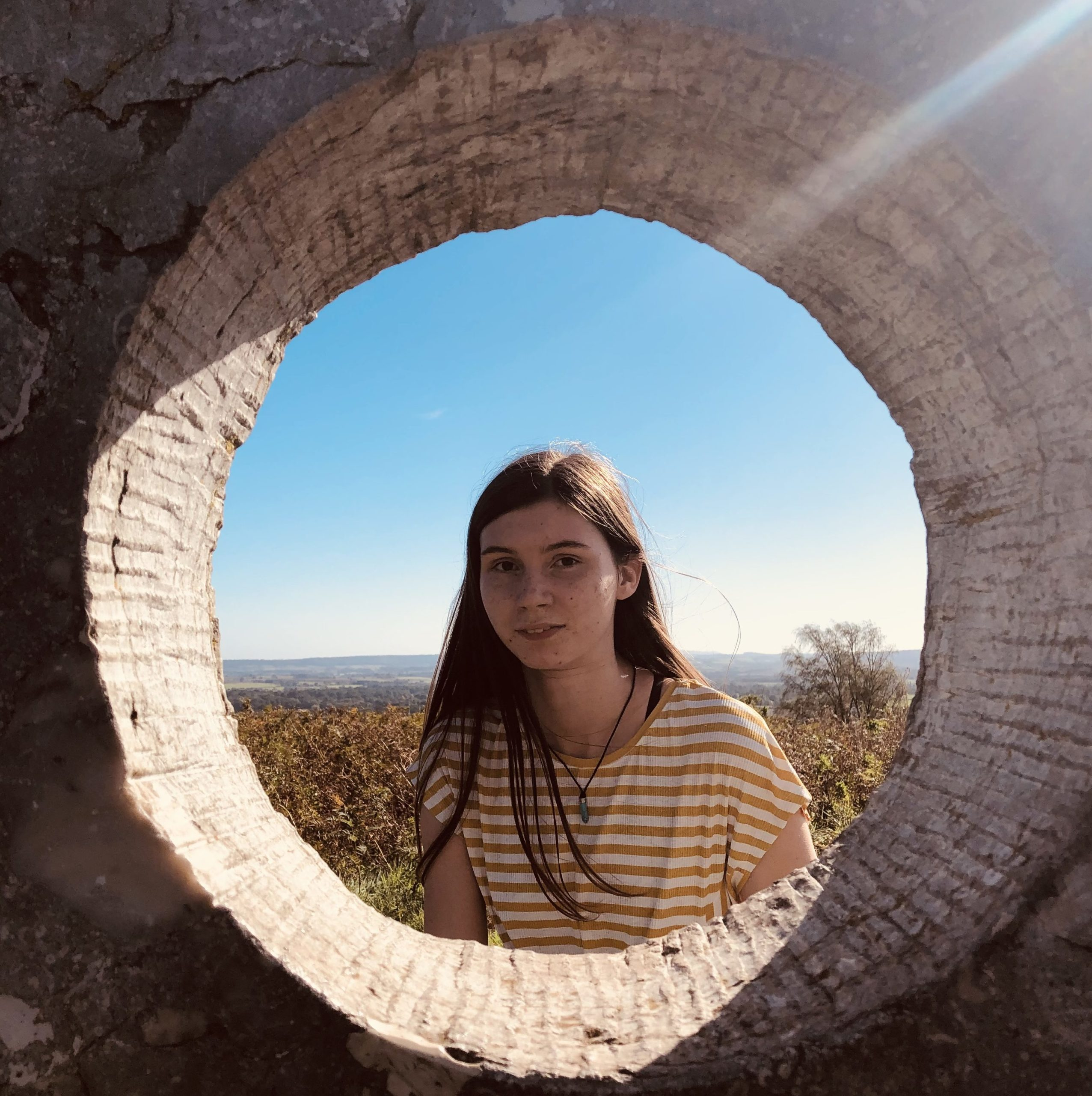 The photo is taken through a hole in a rock to show Sophie, a white person with long brown hair smiling at the camera. She is wearing a yellow t-shirt and blue necklace and there are hills and blue sky visible in the background.
