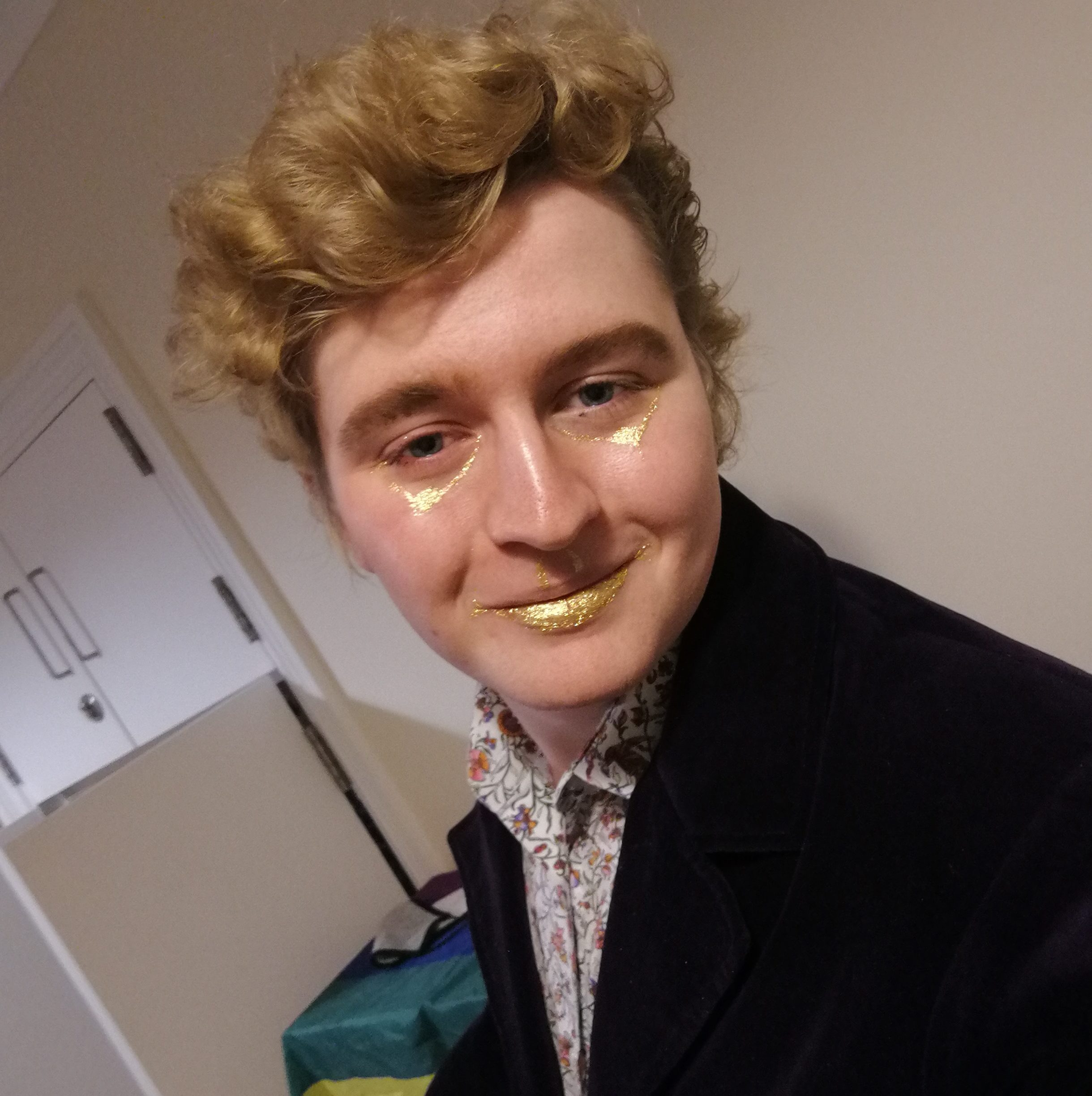 Daniel, a person with curly blonde hair, gold-glitter makeup around the eyes and on the lower lip, wearing a purple velvet coat and a patterned dress-shirt, smiles at the camera while indoors. Behind them is a piece of furniture draped with a pride flag and an open wardrobe.