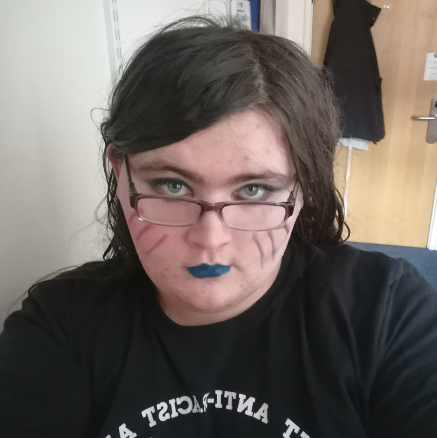 Selfie of Lichen in a bedroom with some eccentric eyeliner, blue lipstick and red and black streaks down their cheeks. They are wearing glasses. and have a black Anti-Flag T-shirt on.