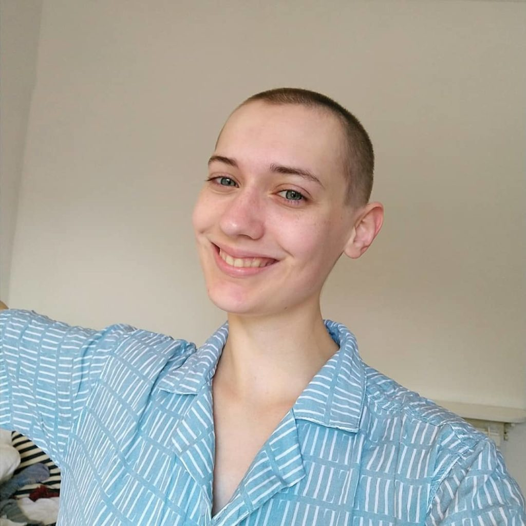 ID: Roma, a white person, is smiling at the camera. They have a shaved head and are wearing a light blue patterned shirt. The photo is from the chest up, and they are in front of a plain light coloured background.